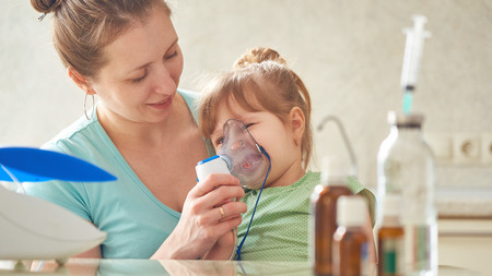woman makes inhalation to a child at home. brings the nebulizer mask to his face. inhales the vapor of the medication. the girl breathes through the mask. medicine on the table. the care of the mother