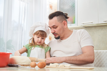 father preparing food with my daughter. a man teaches a child to cook. the process of cooking in a bright kitchen. home cooking is the father of one daughter and love to cook