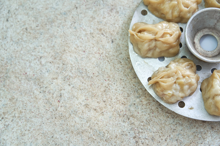 Uzbek national food manta, like dumplings, in a steamer, steamed food. with free text, copy space,