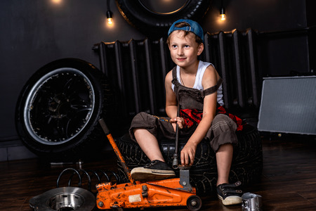 a child in a car repair shop among the wheels and car parts 版權商用圖片
