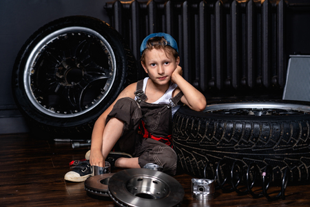a child in a car repair shop among the wheels and car parts Banque d'images