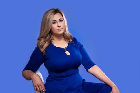 modèle blonde bien roulée avec d'énormes seins en studio sur fond bleu