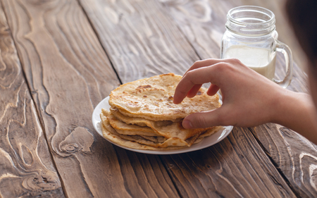 a man is having Breakfast, a mug of milk and a plate of fried corn tortillas on a wooden textured table looking over his shoulder. free text copy space