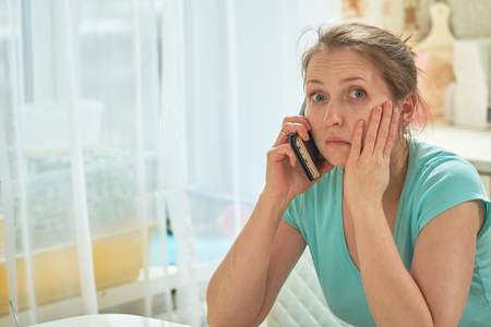 the woman calls the doctor severe toothache. terrible news on the phone. desperate look hopelessness Stockfoto