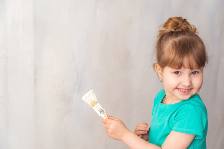 child paints the wall with a white paint brush. finishing work in the premises of the artist paints the walls. repair of the room, premises of the house. the child helps to paint the walls. copy space