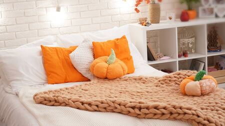 bed with light bed linen covered with a knitted blanket of coarse yarn. in the bedroom on the bed are pumpkin textiles. autumn furnished in light airy style. Imagens