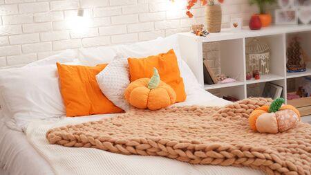 Bett mit leichter Bettwäsche, bezogen mit einer Strickdecke aus grobem Garn. im Schlafzimmer auf dem Bett liegen Kürbistextilien. herbstlich in luftig-leichtem Stil eingerichtet.