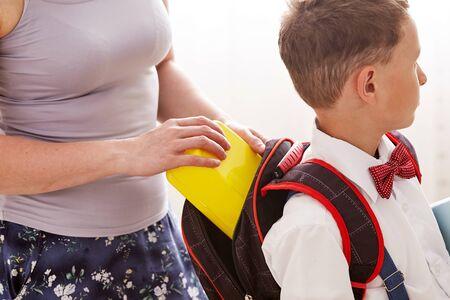 mamá pone un almuerzo escolar empacado en una caja de plástico para su hijo. una madre cariñosa controla la nutrición del niño en la escuela
