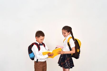 children boy and girl students communicate at school. the girl helps the boy to disassemble the school assignment in the textbook. positive children in school on bedom background