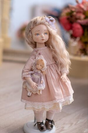 two dolls made by hands from textiles are very similar to living people. designer dolls. is on the stand. creating dolls for the new year holiday. doll mom with a little baby. mother's daughter game