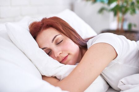 red-haired beautiful girl sleeps hugging a pillow in a light bed in the bedroom. sweet girl sleeping bedroom in the morning light. daytime sleep