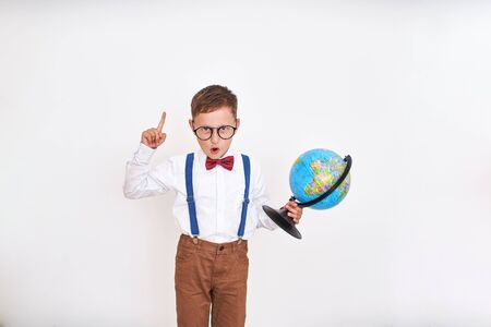 the boy exclaims with his finger up, holding the globe in his hands. came up with the idea. the beginning of the school year.happy child is about to go to school. free text, copy space.back to school Banco de Imagens