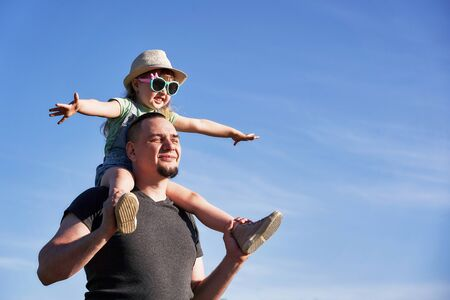 father and daughter on shoulders happily rejoice. dad holding little daughter sitting on the flight mimics the father. the concept of freedom of flight on vacation. free text, copy space.