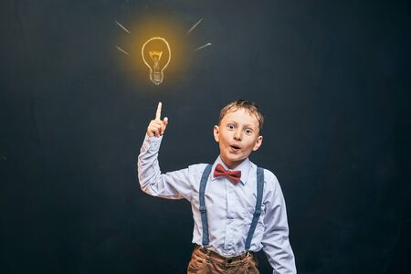 joyful little boy, on a black background. there was an idea and as a symbol the bulb lit up. the child exclaims and points to the top of his hand. free text, copy space.back to school Banco de Imagens