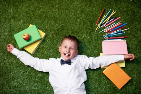 From above a boy with notebooks lies on the grass and smiles. the student is with textbooks and pencils on the lawn. the concept of a positive student.back to school