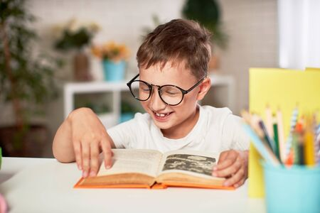 joyful little boy sitting at the table with pencils and textbooks. Happy child pupil doing homework at the table.handsome boy reading a book, home schooling. positive attitude to study