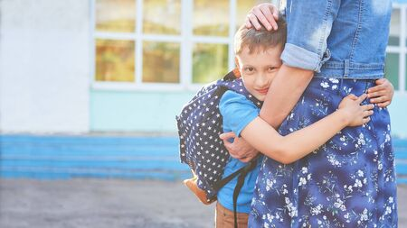 Back to school. Happy mother and son embrace in front of the elementary school. The parent takes the child to primary school. The student goes to study with a backpack. The first day of autumn.