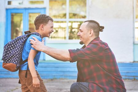 Back to school. Happy father and son in front of the elementary school.The parent takes the child to primary school.The student goes to school with a backpack.The first day of autumn.parental support