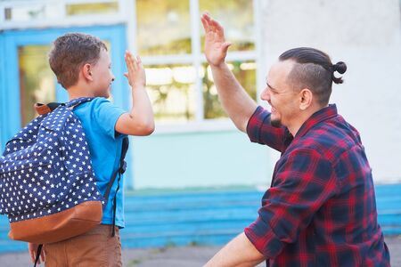 Back to school.Happy father and son are welcome before elementary school. parent meets a child from elementary school.The student goes to school with a backpack.The first day of autumn.clap your hands 版權商用圖片