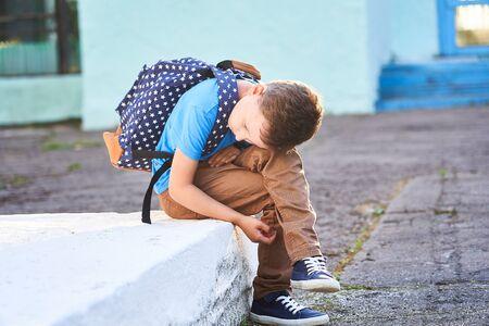 lo scolaro è depresso.torna a scuola.il primo giorno d'autunno.il bambino non è a scuola. apatia nessun amico nella nuova scuola.problema di comunicazione con i loro coetanei.ferire il ragazzo.odio la scuola e gli insegnanti Archivio Fotografico