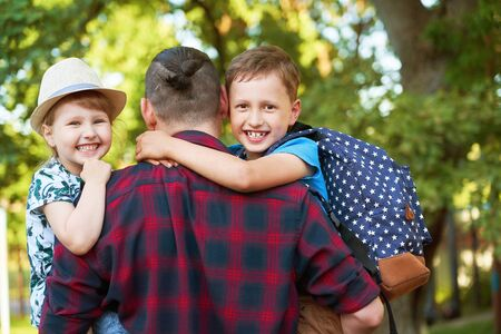 A happy family of father and children.Dad is on the hands of children in primary school.Father, son and daughter in the autumn Park having fun and laughing.The family goes to school outdoors together