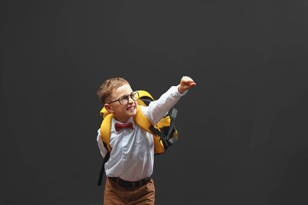 Cheerful smiling baby boy on a dark background raised his hands up demonstrating the desire to win. Leadership concept of the school and supercinema. free text, copy space.back to school Banco de Imagens