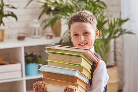 Joyful child holding a stack of textbooks. Selective focus on textbooks. free text, copy space. back to school
