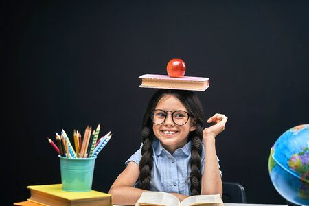 joyful little girl sitting at the table with pencils and books textbooks. Happy child pupil doing homework at the table.beautiful smiling teen girl with pigtails and expressive black eyes with glasses