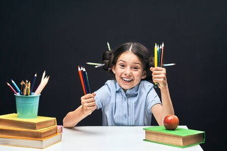 joyful little girl sitting at the table with pencils and textbooks. Happy child pupil doing homework at the table.beautiful smiling girl with funny hair and expressive black eyes