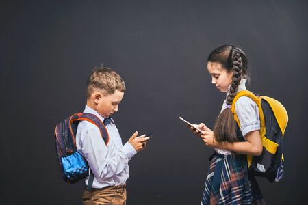 problems of communication of children. dependence on social networks. lack of communication in real life. self-isolation. problems of modern life of children. students communicate through the phone. 版權商用圖片