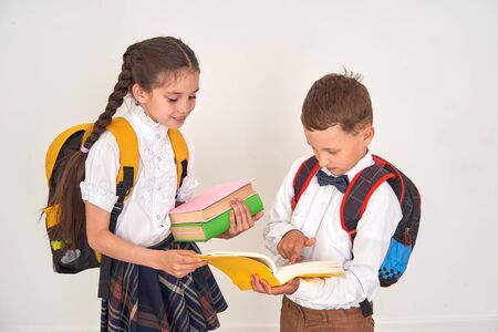 children boy and girl students communicate at school. the girl helps the boy to disassemble the school assignment in the textbook. positive children in school on bedom background.back to school
