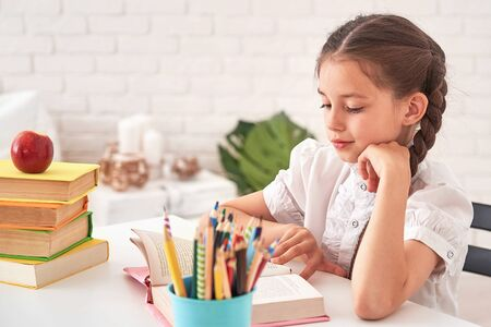 joyful little girl sitting at the table with pencils and textbooks.Happy child pupil doing homework at table.beautiful smiling girl with expressive black eyes.shows a sign of approval.back to school