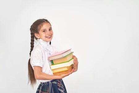 portrait of a beautiful little girl student with a backpack and a stack of books in his hands smiling on a white background. attractive positive. back to school