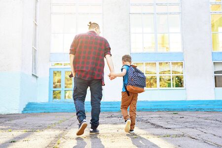 Back to school. Happy father and son go to elementary school. Parent taking child to primary school. Pupil go study with backpack. Beginning of lessons. First day of fall. sun glare