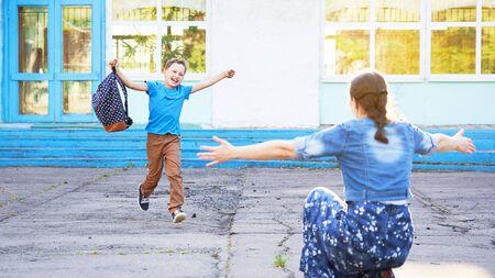 妈妈从小学遇见她的儿子。快乐的孩子跑进他母亲的怀抱。一位快乐的小学生往他的母亲在他的手里拿着一个学校袋子。学校的结束