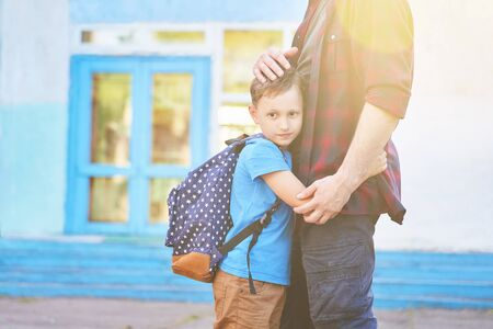 Back to school.Happy father and son embrace in front of the elementary school.The parent takes the child to primary school.The student goes to school with a backpack. The first day of autumn.sun glare