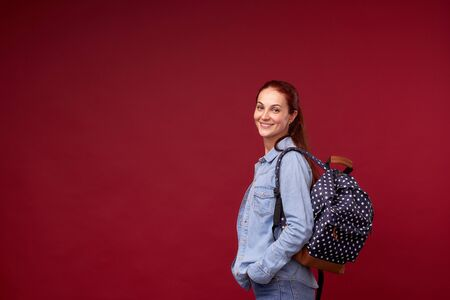 beautiful girl-student. a positive red-haired student in jeans and a backpack behind her shoulders on a red background stands and cute . free space for text