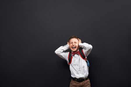 portrait of an emotional child. a boy-schoolboy shouts, a stormy emotional reaction. the concept of the student. shouts back to school. happy back to school. fear of school. free text, copy space