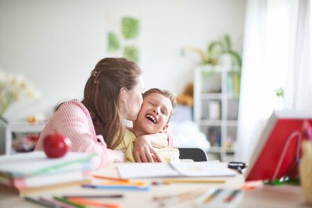 mother helps son to do lessons. home schooling, home lessons. the mother deals with the child, checks the job done. outside school classes with parents. mom kisses happy baby in bright room