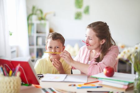 mother helps son to do lessons. home schooling, home lessons. the woman is engaged with the child, checks the job done. outside school classes with parents. mom dabbles with her son in a bright room