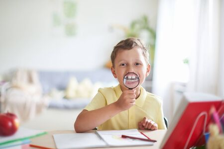 a boy with a magnifying glass in his hands smiles showing his enlarged teeth. funny portrait of a child of shkolnica. childrens fun while studying. preschooler plays distracted from learning.