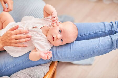 gymnastics baby. woman doing exercises with baby for its development. massage a small newborn baby. love, a caring mother helps the bench to relieve the stress of colic belly,difficulty of gas removal Banco de Imagens