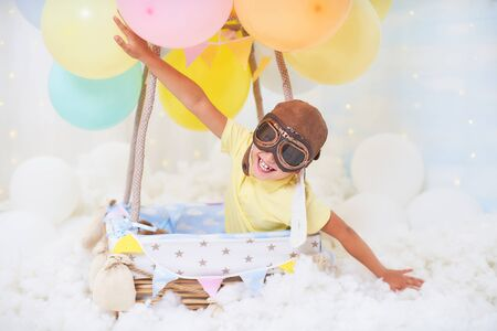 baby boy sitting in a basket of balloon in the clouds, traveling and flying with Aviator hat and glasses. the concept of freedom of creativity or imagination. air scenery dreamy fairy like in a dream 免版税图像