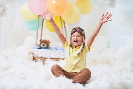 baby boy sitting on cloud next to basket of balloon in the clouds,traveling and flying with Aviator hat and glasses.concept of freedom of creativity or imagination.airy,dreamy fabulous like in a dream