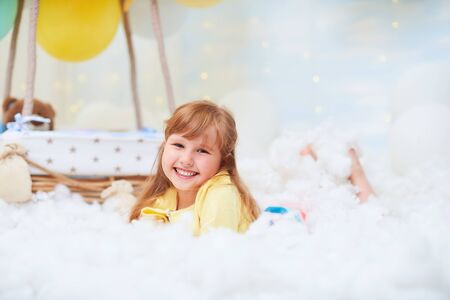 portrait of a baby girl lying on a cloud next to a basket of balloon in the clouds, traveling and flying in dreams.concept of freedom of creativity or imagination.airy,dreamy, fabulous,like in a dream