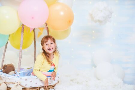 baby girl sitting in a basket of balloon in the clouds, traveling and flying with Aviator hat and glasses. the concept of freedom of creativity or imagination. air scenery dreamy fairy like in a dream Banco de Imagens