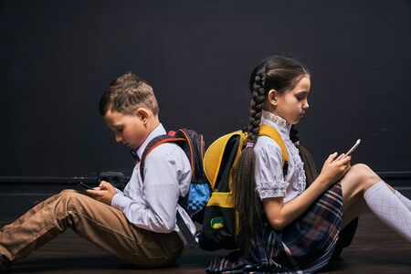 problems of communication of children. dependence on social networks. lack of communication in real life. self-isolation. problems of modern life of children. students communicate through the phone. Banco de Imagens