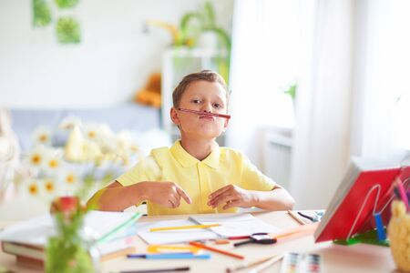 the boy does his homework at home. a happy child at a table with school supplies smiles funny and plays with a flamaster imitating . positive student in a bright room with a pencil in his hands.