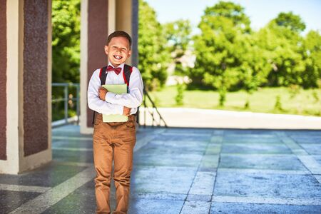 the child goes to primary school. portrait of a happy child with a briefcase on his back. the concept of the student is holding the book happy to be back in school. the first day of autumn, copy space