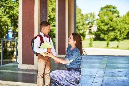 mother accompanies the child to school. mom encourages the student to accompany him to school. caring mother looks tenderly at her son going to school.positive boy having fun going to primary school 免版税图像